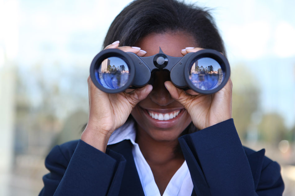woman in business suit looking through binoculars