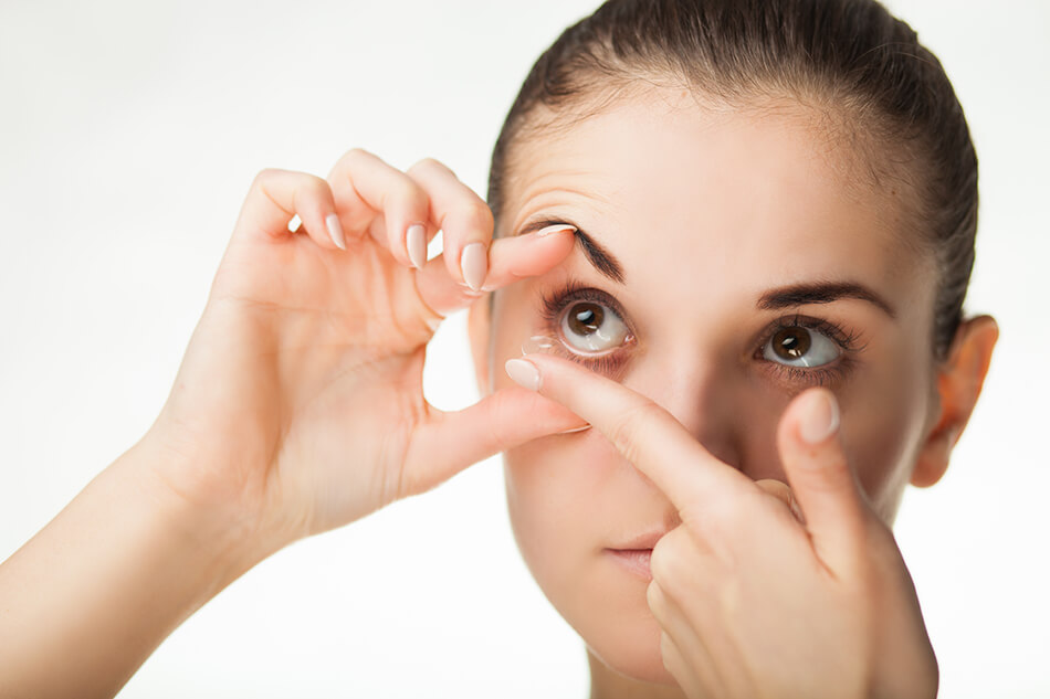 woman holding eye open while inserting contact lenses