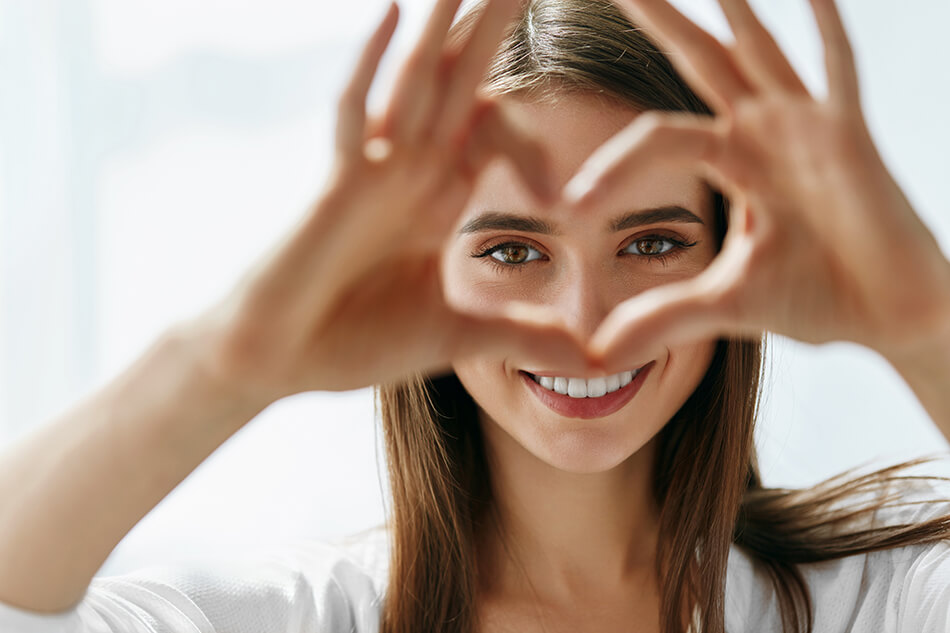 woman making a heart sign with her hands framing her eyes