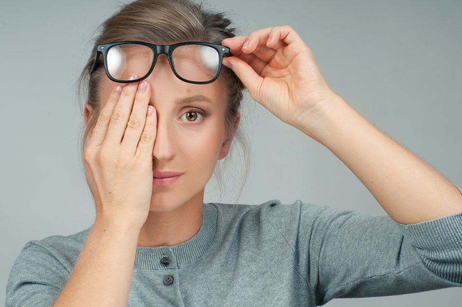 woman wearing glasses covering one eye