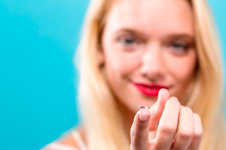 woman blurred in background happy and holding contact lens on tip of finger