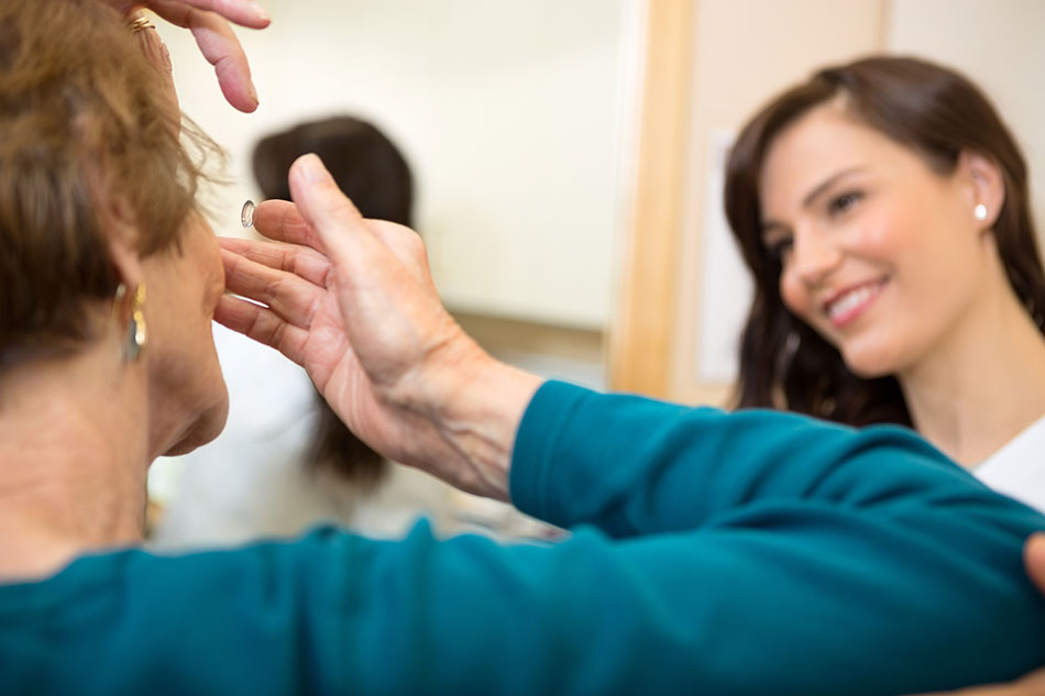 Woman inserting contact lens with guidance from young female eye doctor