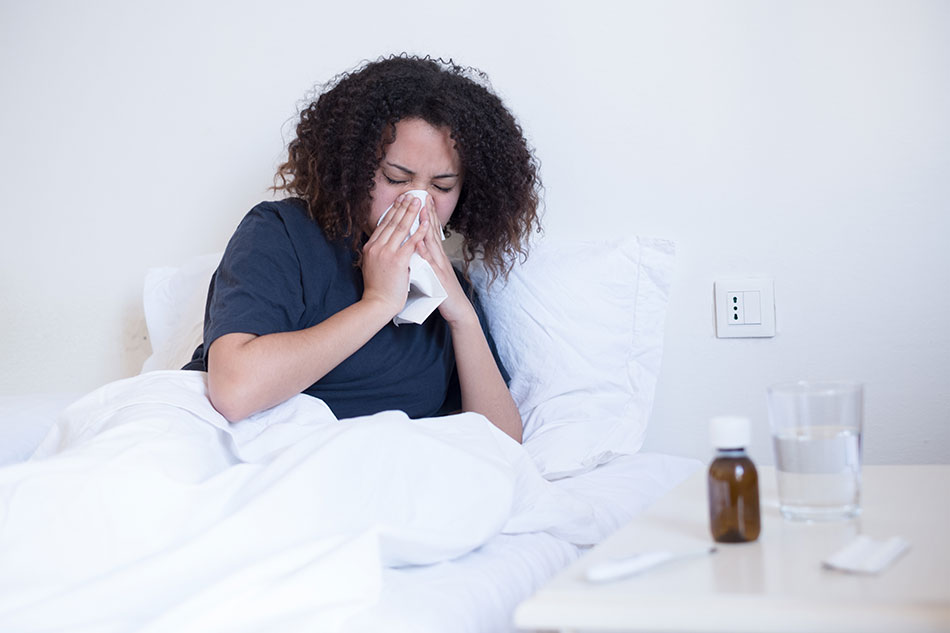 woman sick in bed blowing nose