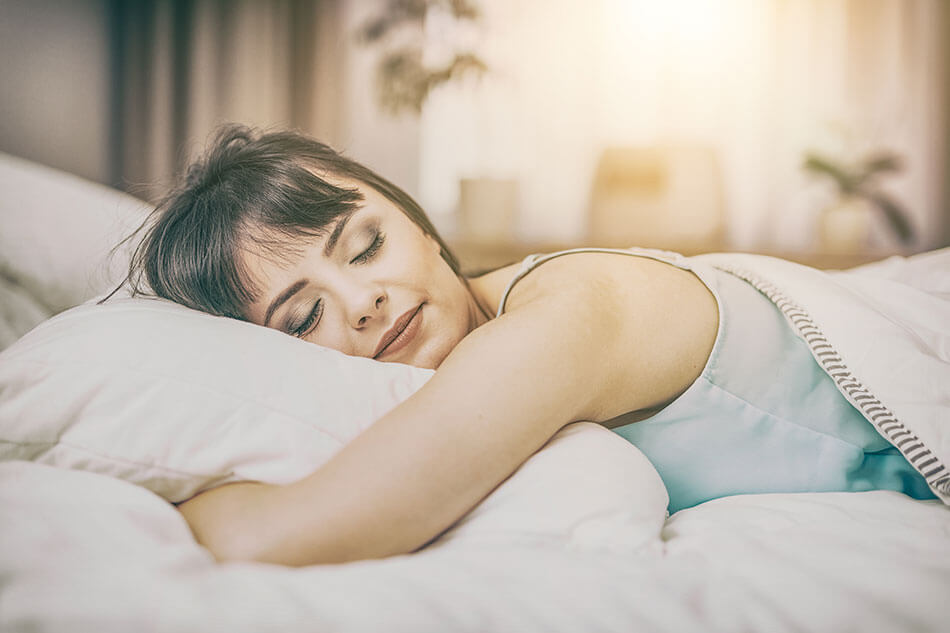 woman sleeping on stomach resting head on pillow