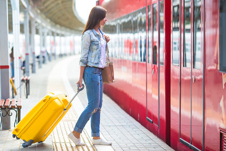 woman pulling suitcase getting on train