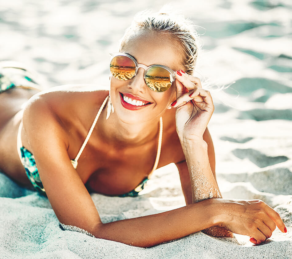 Woman on beach wearing sunglasses for eye protection