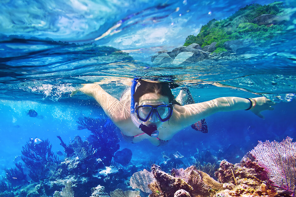 young woman snorkeling in tropical water