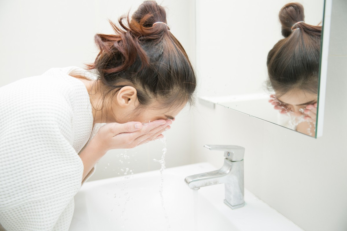 woman washing face at bathroom sink