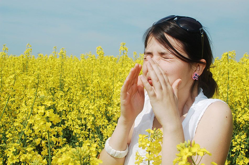 Woman surrounded by yellow flowers and sneezing