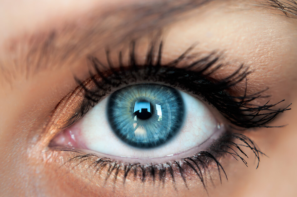 close up of woman's eye with beautiful blue colored contact lens