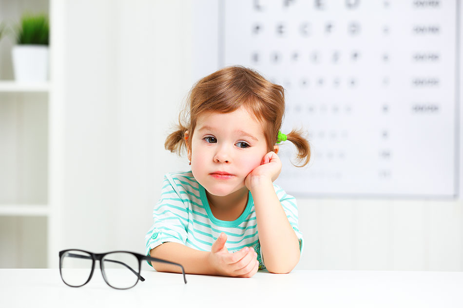 young child with glasses in front, eye chart in background