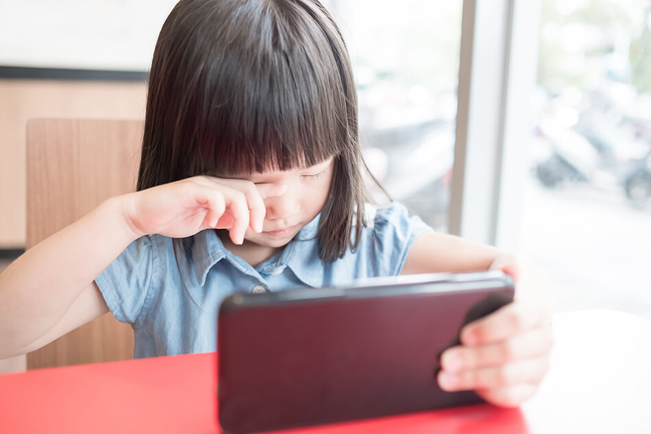 young girl rubbing eyes while holding a computer tablet
