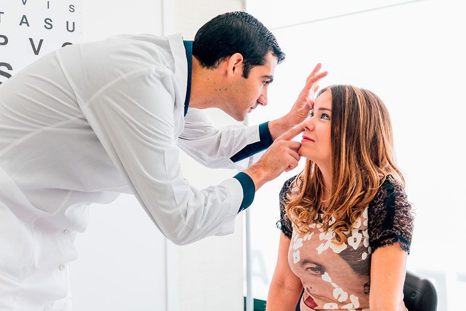 Young woman getting eyes examined by eye doctor